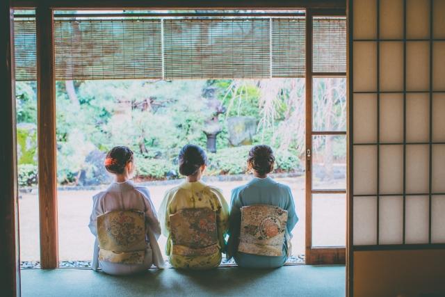 着物を着た三人の女性が座っています